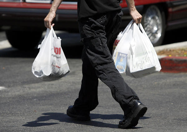 A shopper uses plastic bags to carry his groceries to his car at the Vons on Glendale Avenue in Glendale.