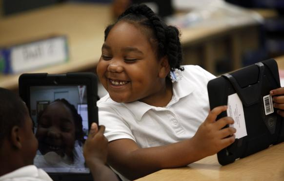 Tiannah Dizadare smiles as she works with classmate Avery Sheppard as they explore their new LAUSD-provided iPads.