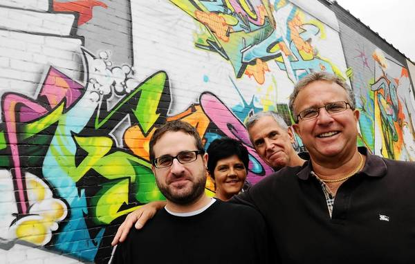 Jerry's Artarama is celebrating its 20th anniversary. Here, owner Jeffrey A. Shoham, right, is photographed with, from left, son and store manager Andrew J. Shoham, custom framer Budinca Alexandru, and general manager Chet Terry in front of a mural painted on the side of the store in Elmwood several years ago.