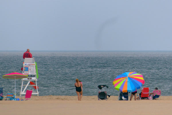 A sparse beach crowd enjoy a calm ocean in lower Ocean City.