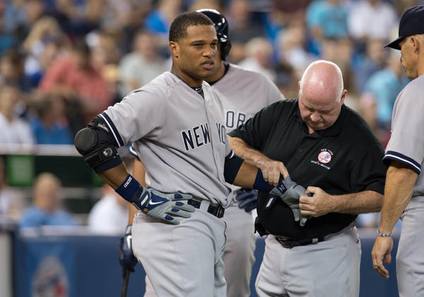 New York Yankees second baseman Robinson Cano is looked at by trainer Steve Donohue after being hit with a wild pitch by Toronto Blue Jays starting pitcher J.A. Happ.
