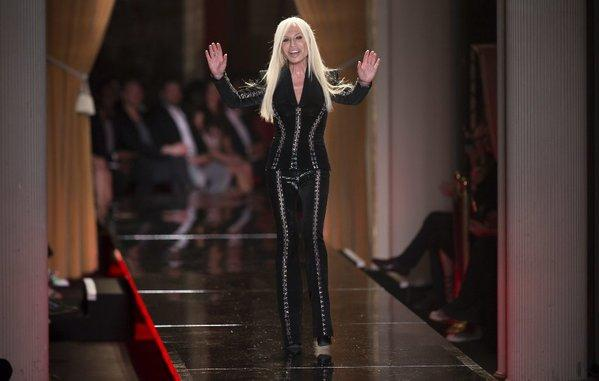 "Donatella Versace waves to the audience at the Versace Haute Couture show in Paris. Apparently the designer approves of Lady Gaga's song ""Donatella,"" a track on the singer's forthcoming ""Artpop"" album."