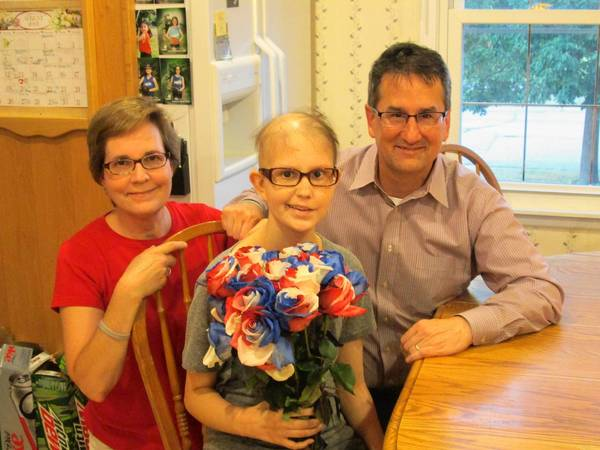 Emily Wheeler, who has a rare form of brain cancer, holds flowers that she received during a surprise parade in front of her home. Her mother, Mary (left), and father, Steve (right) said the parade helped lift her spirits.