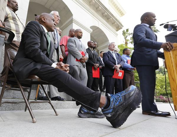 Former NFL linebacker Reggie Williams stretches his surgically repaired leg out as he listens to NFL Players Assn. executive director DeMaurice Smith speak in Sacramento back in April.