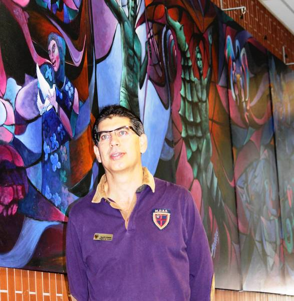 "Agustin Valdivia, with the Puerto Vallarta tourism board and leader of the delegation to Highland Park, in front of a mural done in acrylics on the wall of the HPHS cafeteria. It's about about 35 feet long and 8 feet high, completed in April 2004 by Mexican artist Javier Nino, and is entitled, ""Amistad,"" which means friendship."