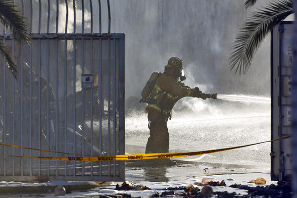 Firefighter shoots water Wednesday at a fire at a Santa Ana warehouse.
