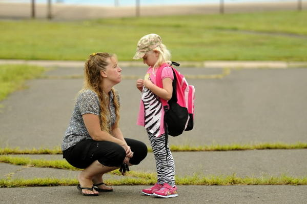 Jill Terry tries to settle some apprehension by her daughter Leah Terry, 5, in the Waddell School playground before the children entered for the first day of class Wednesday morning.