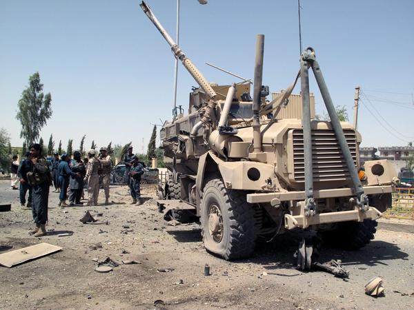 Afghan security officials and NATO soldiers inspect the scene of a suicide bomb attack on a NATO convoy in Lashkar Gah, the provincial capital of volatile Helmand province.