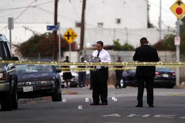 Police tape marks the area where two people were killed in a shooting Tuesday in South Los Angeles.
