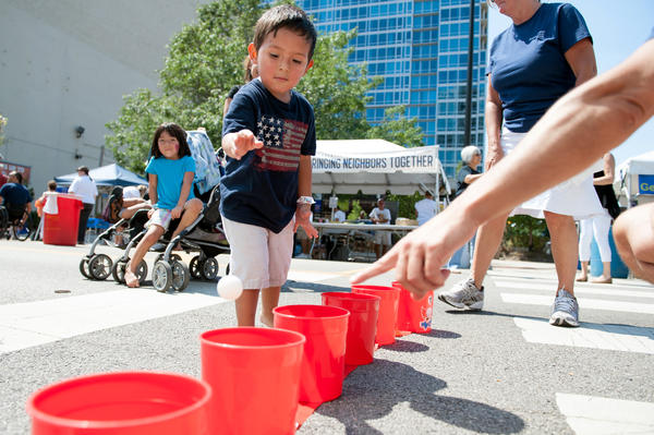 Two-year-old Yazmani Hernandez tosses a ping pong ball into a bucket while playing one of the games during the Bash on Wabash street festival in Chicago's South Loop neighborhood on Aug. 24, 2013.