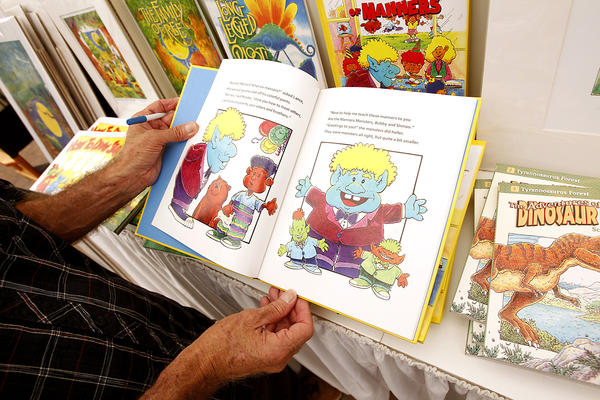 Scott Sutton thumbs through one of his books at the Art-A-Fair. Sutton is a children's book author and illustrator and encourages children to read in the process.