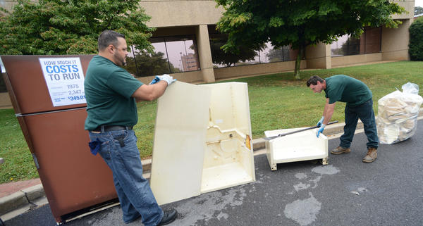 Keith Yanchek, left, and Ken Sproat of JACO Environmental tear down a refrigerator to show the process of how they recycle old refrigerators.