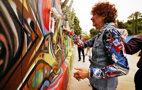 Barbara Black cries as she paints over a mural on her alley fence in 2011, which was declared an illegal sign. The city ordered the Valley Village artwork removed.