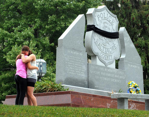 Two young women mourn at the wreath  laying ceremony in front of the Police Officer monument at the Baltimore County Circuit Courthouse in honor of Police Officer First Class Jason Schneider who was killed today in Catonsville while serving a warrant.