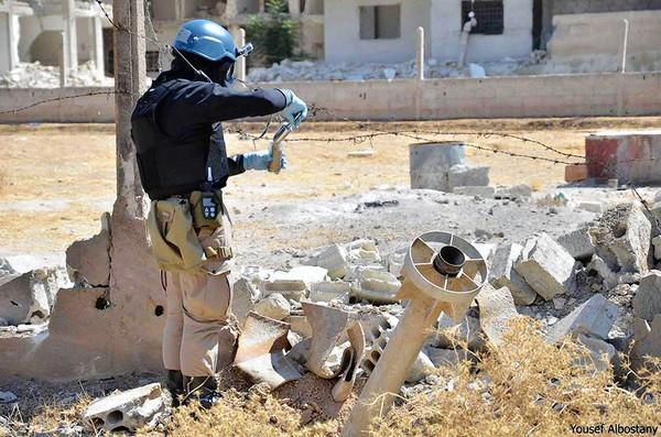 A member of a United Nations chemical experts team takes a sample of soil near a missile that landed in Ain Terma, outside Damascus, the Syrian capital. British lawmakers said they didn't want to vote on military intervention until the team had issued its report on the alleged use of chemical weapons by the Syrian government.