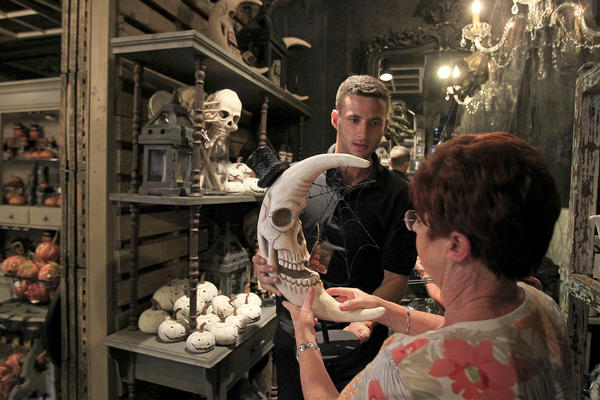 Employee Mick Mulhall, center, helps Josie Carlevato, right, of Chino Hills, take a closer look at a skull moon, by artist Bethany Lowe, during Roger's Gardens' Halloween Boutique Night Gallery on Wednesday.