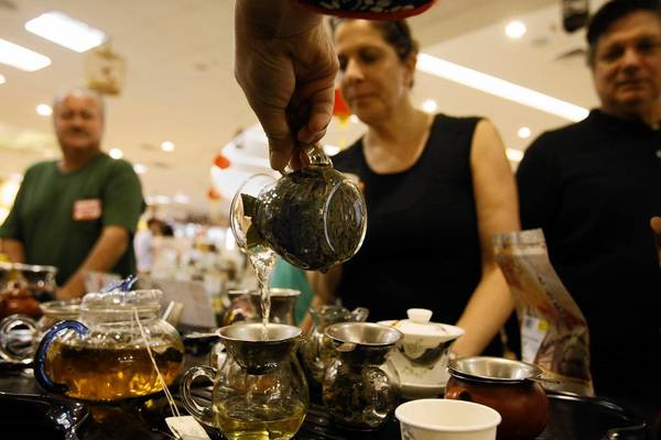 Irit Eliyahu, center, and Don Solomon, right, observe Chinese tea being poured at Wing Hop Fung in Monterey Park during a stop on an Esotouric Bus Adventure immigration tour.