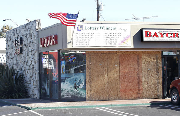 Plywood boards cover the front of Baycrest Liquor after a truck crashed through the window and stole an ATM machine early Wednesday. The store is known for its good luck in lotto winnings.