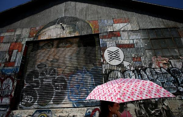 A woman walks past an old corrugated metal structure in the downtown Los Angeles arts district.