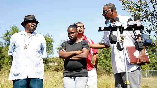 Keisha Summeries (center), mother of 5 month-old Joshua Summeries, listens during a press conference outside the Advanced Disposal Services landfill in Zion Wednesday where she called for the search for Joshua's body to continue. The men in the photo are Rev. Arthur Devost, Paul McKinley, and Clyde McLemore (from left).