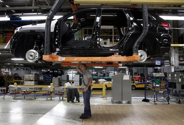 U.S. economic growth accelerated in the second quarter. Above, a worker checks a vehicle at a Chrysler factory in Detroit.