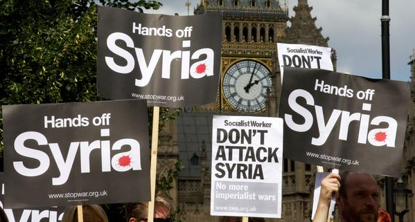 Demonstrators hold up placards protesting against any British military involvement in Syria outside the Houses of Parliament in London.