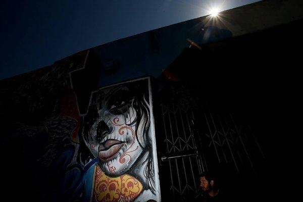 A man walks past graffiti art on the exterior of a warehouse in the downtown Los Angeles Arts District.