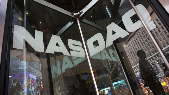 A security guard stands at the door of the Nasdaq the day the exchange experienced a three-hour trading outage.