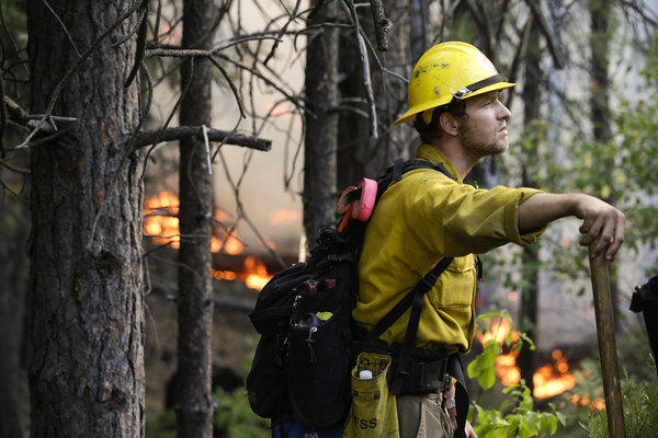 Firefighter Brandon Wenger stands along California 120 while monitoring a backfire intended to impede the Rim fire near Yosemite National Park.