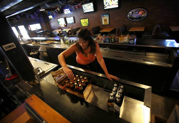 Bartender Bonnie Moulton gets the bar redy for the day's business at Burton's Bar in Orlando on August 27, 2013.