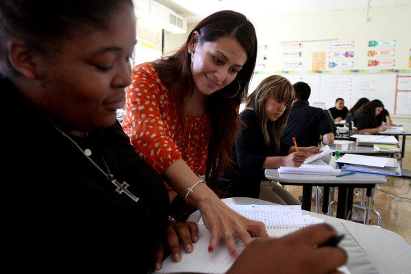 Teacher Cassandra Villa compliments student Anisha Steward, left, 17, during English class at Animo College-Prep on the campus of Jordan High School in the Los Angeles neighborhood of Watts. The students have achieved the highest gains in school performance in the state.