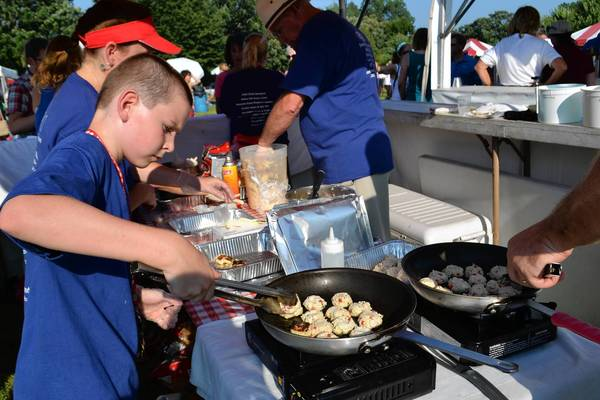 Sam Hannagan flips a crab cake at the Diamond Fresh Seafood booth at Lake Zurich's Taste of the Towns. His mother Carol is the owner.