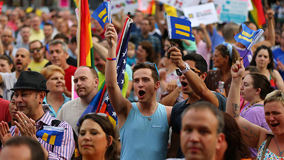 Mitchell Miller, in blue, cheers with his partner Frank Castillo, right, during a gay rights rally after the day's two Supreme Court rulings related to gay marriage Wednesday, June 26, 2013 at Halsted Street and Roscoe Street in Chicago. The two were joined in a civil union in February of 2012.