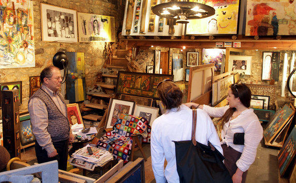 Tourists shop for paintings at an art store in Damascus, the Syrian capital.