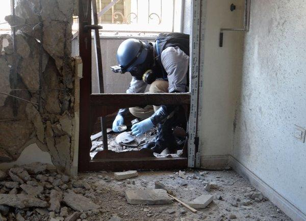A United Nations chemical weapons expert collects samples in the eastern Ghouta region outside the Syrian capital, Damascus.