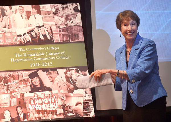 "Diane Weaver, author of ""The Community's College: The Remarkable Journey of Hagerstown Community College 1946-2012,"" unveils the book's cover Tuesday at Hagerstwon Community College's Kepler Theater."