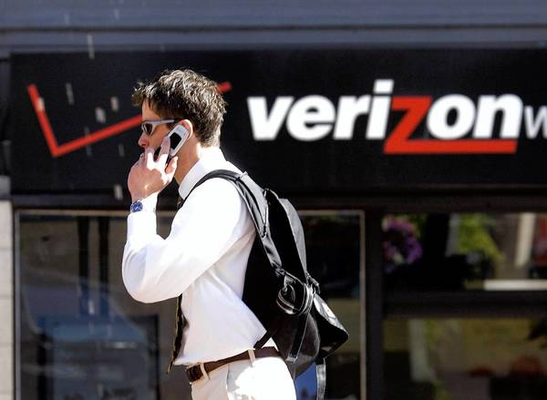 A man talks on his cellphone as he walks past a Verizon store in Portland, Ore. Verizon may be close to buying Vodafone's 45% stake in Verizon Wireless, a joint venture established by the two companies in 2000.