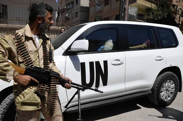 A Free Syrian Army fighter helps fellow fighters escort a United Nations convoy of chemical weapons experts Wednesday at one of the sites of an alleged chemical attack in Zamalka, a suburb of Damascus.