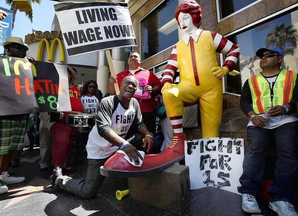 Part-time McDonald's maintenance worker Robert Wideman, 55, shines the shoe of Ronald McDonald during a protest outside a Hollywood McDonald's.