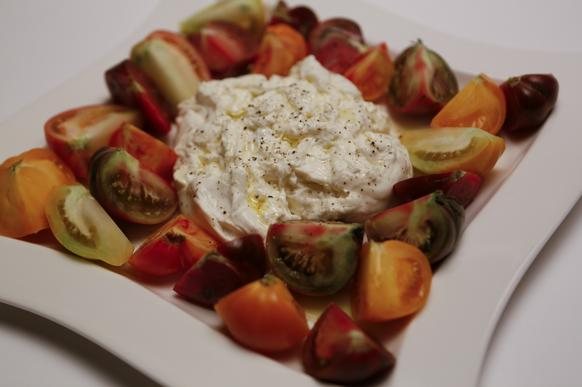 Baked tomatoes with garlic and a scoop of olive-oil-drizzled <i>burrata</i>.