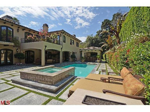 The Mediterranean-style house opens to manicured grounds and a swimming pool.
