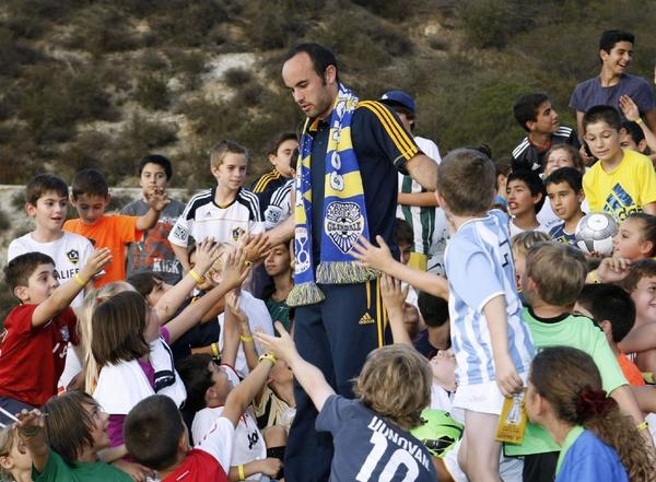 United States National Team striker Landon Donovan gives high fives to children who participated in a Los Angeles Galaxy-sponsored soccer clinic at the Glendale Sports Complex on Thursday. About 150 AYSO players participated. (Raul Roa/Staff Photographer)