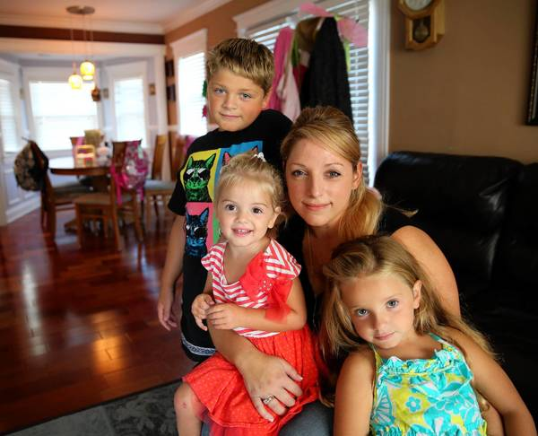 Becky Giannelli, with her kids Gio, 10, from left, Mia, 3, and Cece, 5, at their Glendale Heights home, said she wishes that the HPV vaccine had been recommended when she was a preteen. She was diagnosed with cervical cancer two years ago.