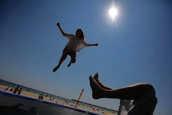 Youths play on a trampoline on the beach in La Baule