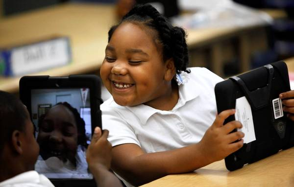L.A. Unified has begun providing iPads to students in hopes of boosting achievement. Above, Avery Sheppard, left, views a smiling Tiannah Dizadare on his L.A. Unified-provided iPad in their classroom at Broadacres Avenue Elementary in Carson.