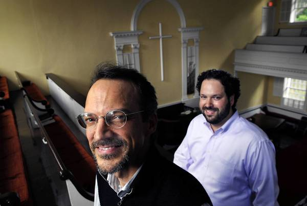 The Rev. Jeffrey Braun, left, senior pastor of the First Congregational Church, United Church of Christ, and Rabbi Josh Whinston of Temple Beth David, both in Cheshire, are seated in the sanctuary of the Congregational church. Rabbi Whinston will be bringing his congregation to the church for the High Holy Days in September since his building is too small to handle the crowds. In deference to the Jewish congregation, the cross behind them will be removed for the services.