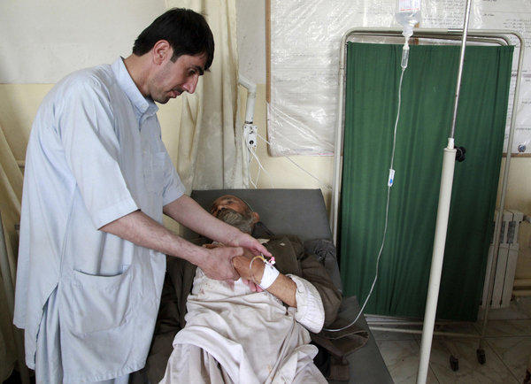A man who was injured in a suicide attack lies on a hospital bed in the northern Afghan province of Kunduz.