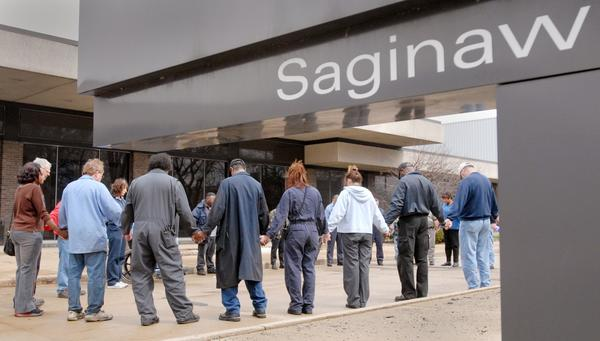A group of workers from Delphi Energy & Chassis Saginaw Operations in Michigan prays outside the plant during a break in 2006.
