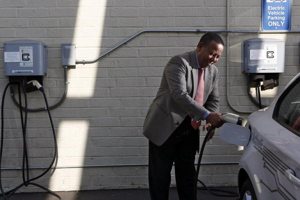 Yesewlik Leo Ayalew, chief financial officer of Calstart, connects his electric vehicle and a charger at his Pasadena, Calif., workplace, a clean transportation consulting firm.