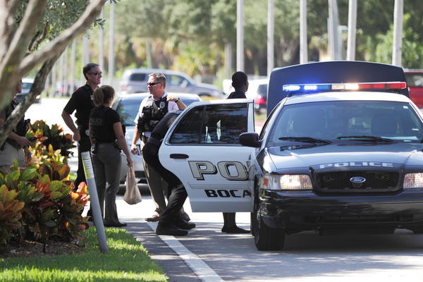 A burglary suspect, who has not been identified by police, is searched before being put in a Boca Raton Police car on Friday off Jim Moran Boulevard in Deerfield Beach.